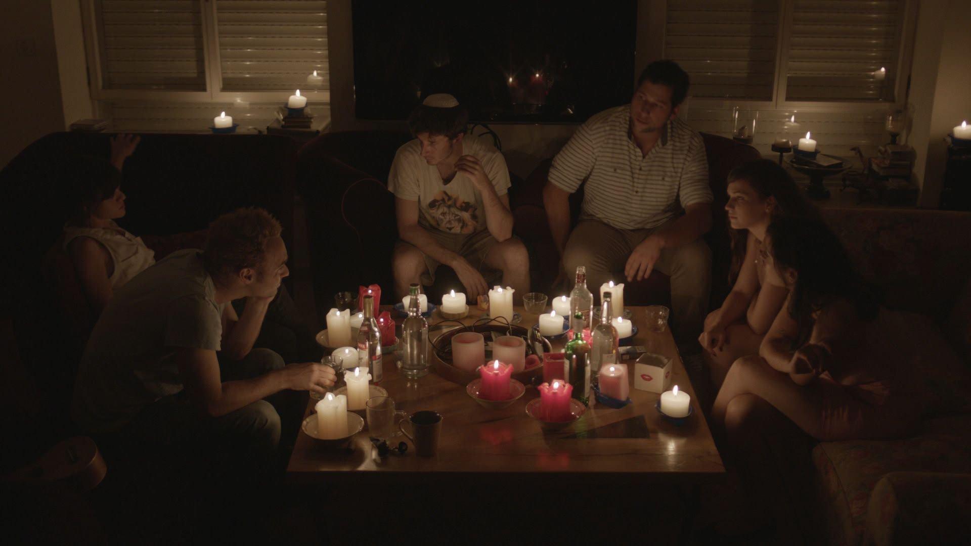 תמונה מתוך סופעולם. חבורת צעירים יושבת סביב השולחן לאור נרות.