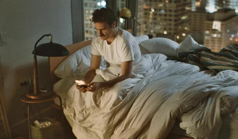 תמונה מתוך היא. גבר בודד יושב במיטה, מחזיק את הטלפון שלו.