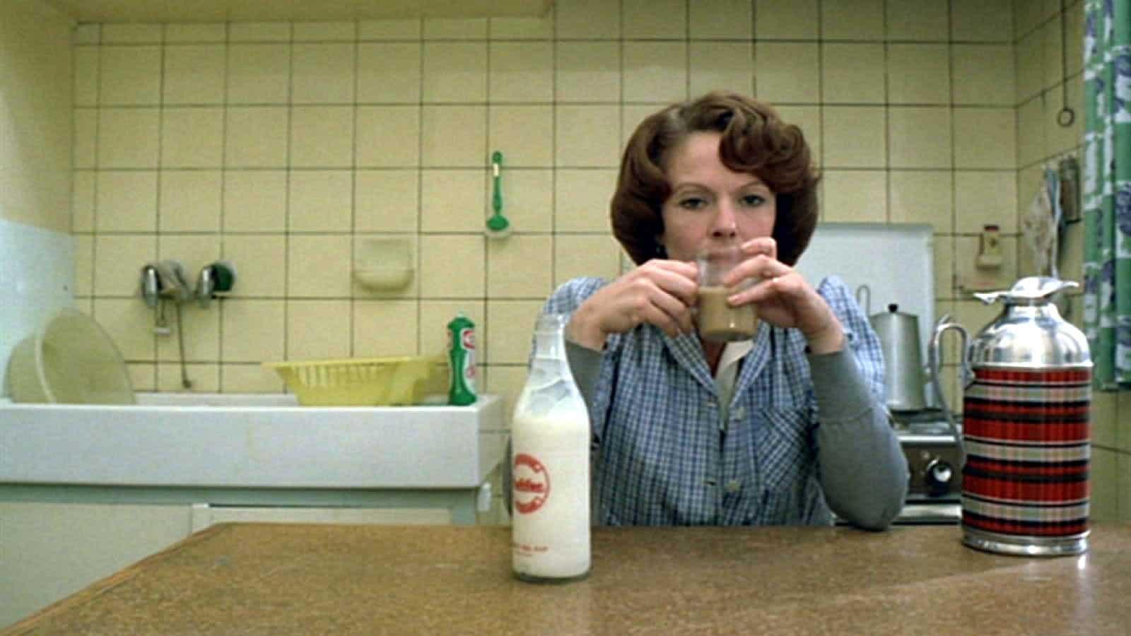 תמונה מתוך ז'אן דילמן. אישה יושבת במטבח ושותה קפה.