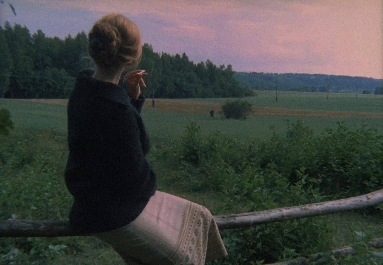 """מתוך הסרט """"המראה"""". אישה יושבת על גדר ומסתכלת על גבר רחוק, הרוח מקשרת ביניהם."""