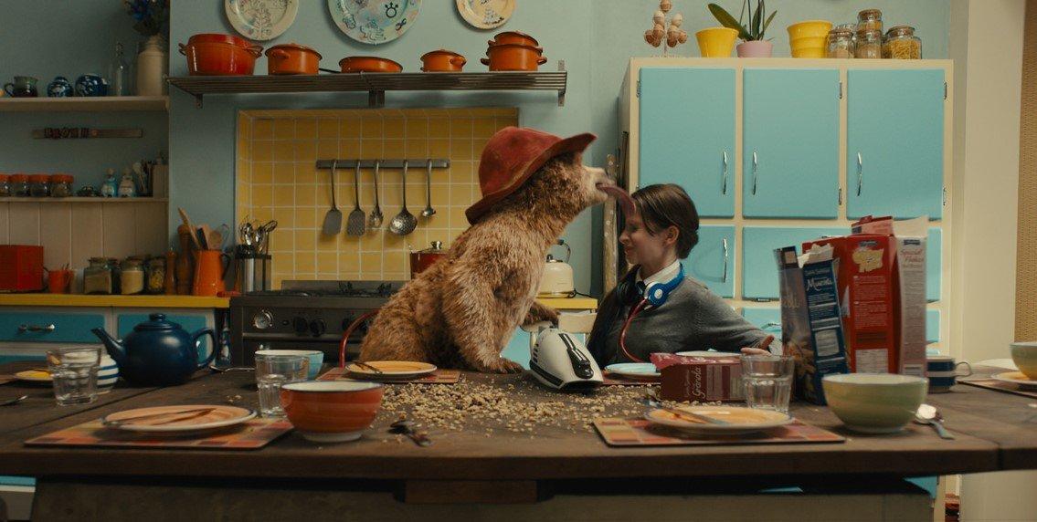 תמונה מתוך פדינטגון. הדב פדינגטון מלקק ילד במטבח מבולגן.