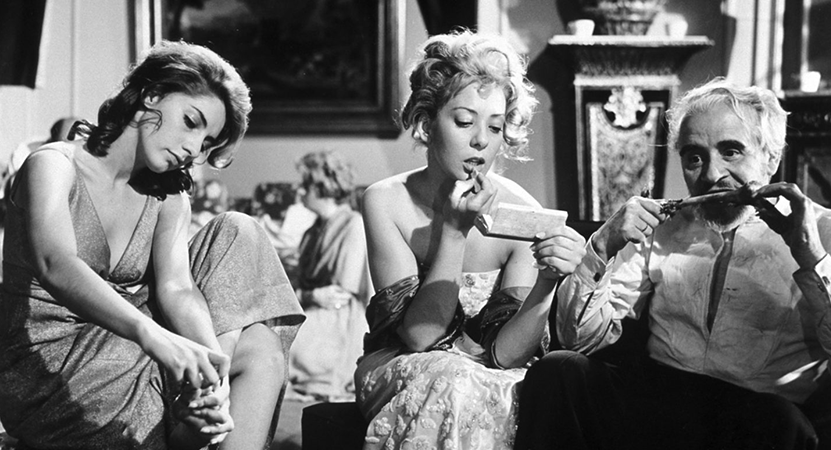 תמונה מתוך המלאך המשמיד. גבר אוכל, אישה אחת מתאפרת ואישה שניה מורחת לק.